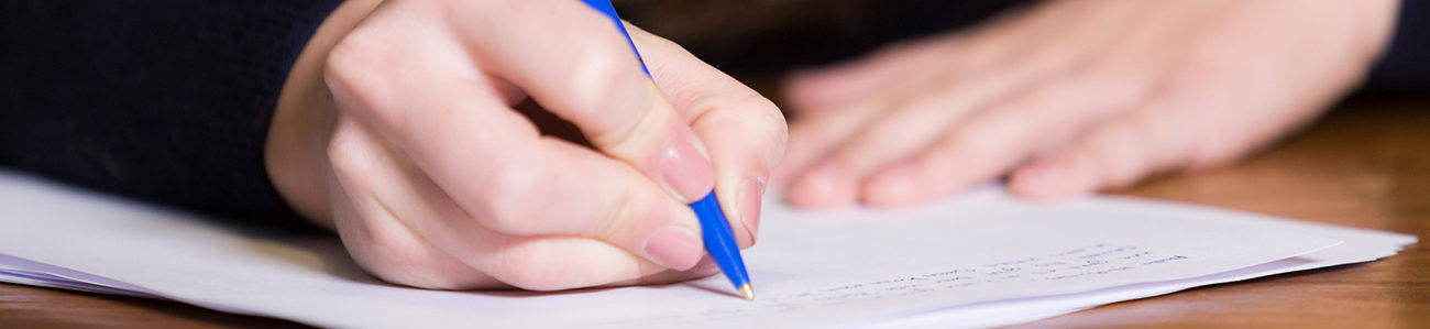 A white lady using a blue pen to write on a piece of paper.